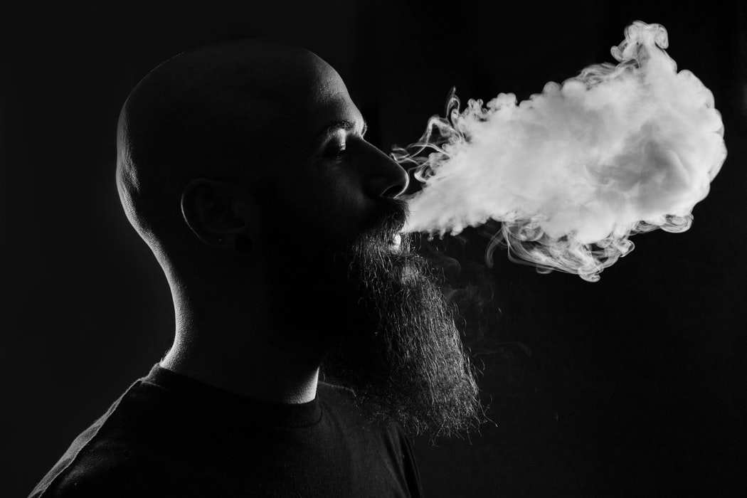 black and white photo of man blowing out vape